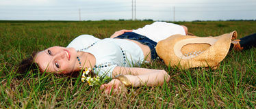 Schöne junge Frau, die im Gras liegt Lizenzfreies Stockbild
