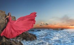 Schöne junge Frau, die im luxuriösen langen Kleid auf dem Strand aufwirft stockfoto