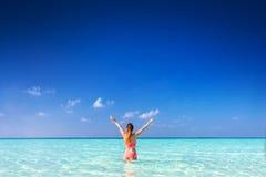 Schöne junge Frau, die im Ozean mit den Händen angehoben steht maldives Lizenzfreie Stockbilder
