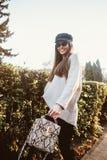Schöne junge Frau, die im Park nahe der Hecke aufwirft stockfoto