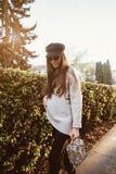 Schöne junge Frau, die im Park nahe der Hecke aufwirft stockfotografie