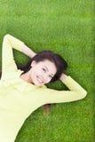 Schöne junge Frau, die im Park niederlegt Lizenzfreie Stockbilder