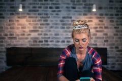 Schöne junge Frau, die im Smartphone an der gemütlichen Wohnung grast Lizenzfreie Stockfotos
