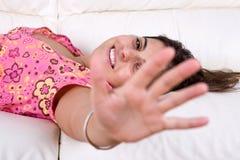 Schöne junge Frau, die im Sofa lächelt Stockfotos