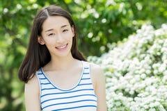 Schöne junge Frau, die im Sommer genießt Stockfotografie
