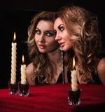 Schöne junge Frau, die im Spiegel nahe drei Kerzen schaut Stockbild