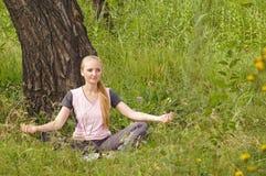 Schöne junge Frau, die im Wald unter dem Baum sich entspannt Lizenzfreie Stockfotografie