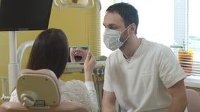 Schöne junge Frau, die im zahnmedizinischen Stuhl in der Klinik sitzt der Doktor überprüft die Mundhöhle Bildmenge zum Sepiaton f stock video