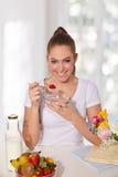 Schöne junge Frau, die Joghurt mit Erdbeere isst Stockfotos
