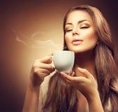 Schöne junge Frau, die Kaffee genießt lizenzfreie stockfotos