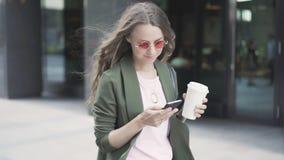 Schöne junge Frau, die Kaffee zum Mitnehmen und das Nettosurfen, gehend in Straße hält stock video footage