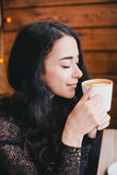 Schöne junge Frau, die Kaffeecappuccino mit Schaum nahe Fenster genießt Lizenzfreies Stockfoto