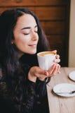 Schöne junge Frau, die Kaffeecappuccino mit Schaum nahe Fenster genießt Lizenzfreies Stockbild