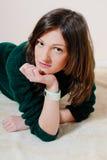Schöne junge Frau, die Kamera in den Strickwaren betrachtet Stockfoto