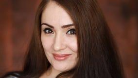 Schöne junge Frau, die die Kamera lächelt, blinzelt und betrachtet Porträt eines Brunettemädchens mit Braun mustert Nahaufnahme stock footage