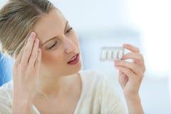 Schöne junge Frau, die Kopfschmerzen hat Stockfotos