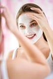 Schöne junge Frau, die kosmetische Maske auf ihrem Gesicht tut Stockfoto