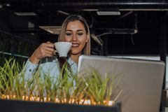 Schöne junge Frau, die an Laptop und trinkendem Kaffee arbeitet stockfotografie