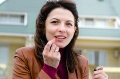 Schöne junge Frau, die Lippenstift anwendet stockfotografie