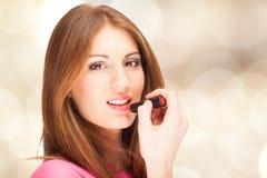 Schöne junge Frau, die Lippenstift anwendet stockfotos