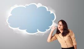 Schöne Frau, die mit abstraktem Wolkenkopienraum gestikuliert Lizenzfreies Stockfoto