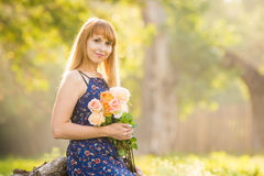 Schöne junge Frau, die mit Blumenstrauß von Rosen in den Händen auf einem Hintergrund von grünem sonnigem verwischt schaut Lizenzfreie Stockfotos