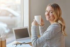 Schöne junge Frau, die mit Computer arbeitet, Schale hält und Kamera betrachtet Stockfoto