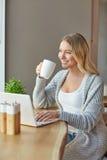 Schöne junge Frau, die mit Computer am Café, eine Schale des Getränks halten arbeitet Lizenzfreie Stockfotos