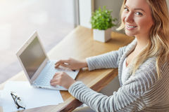 Schöne junge Frau, die mit Computer am Café schreibt auf einer Tastatur und betrachtet Kamera arbeitet Beschneidungspfad eingesch Stockfotos