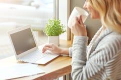 Schöne junge Frau, die mit Computer an trinkendem Kaffee des Cafés arbeitet und auf einer Tastatur schreibt Stockbilder