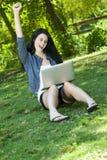 Schöne junge Frau, die mit Computer zujubelt Stockfotos