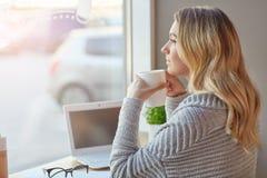 Schöne junge Frau, die mit dem Computer hält eine Schale des Getränks und durchdacht heraus schaut das Fenster arbeitet Lizenzfreie Stockfotografie