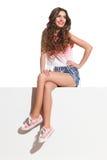 Schöne junge Frau, die mit den Beinen gekreuzt sitzt Lizenzfreie Stockfotos
