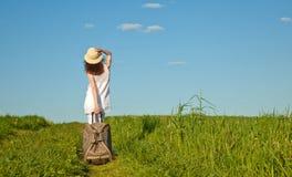 Schöne junge Frau, die mit einem Koffer geht Stockfotografie