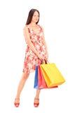Schöne junge Frau, die mit Einkaufstaschen aufwirft Stockfotos