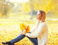Schöne junge Frau, die mit gelben Ahornblättern im warmen sonnigen Herbst sitzt Lizenzfreies Stockfoto
