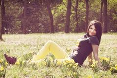 Schöne junge Frau, die mit gelben Narzissen auf der Wiese aufwirft Stockfotografie