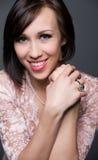 Schöne junge Frau, die mit gesundem Gesicht und sauberer Haut auf grauem Hintergrund lacht Lizenzfreies Stockbild