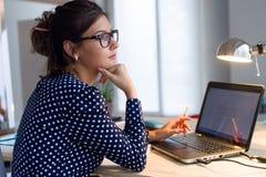 Schöne junge Frau, die mit Laptop in ihrem Büro arbeitet Stockbilder