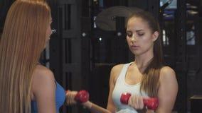 Schöne junge Frau, die mit persönlichem Trainer an der Turnhalle ausarbeitet stock footage