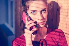 Schöne junge Frau, die am Mobilhandy spricht Lizenzfreies Stockfoto