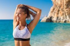 Schöne junge Frau, die nach Training auf dem Strand ausdehnt stockfotos