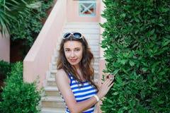 Schöne junge Frau, die nahe einem grünen Busch in einem Park steht Lizenzfreies Stockfoto