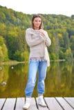 Schöne junge Frau, die nahe einem See sich entspannt Stockfotos