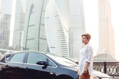 Schöne junge Frau, die nahe schwarzem Auto auf Wolkenkratzerhintergrund steht Stockfotos