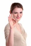 Schöne junge Frau, die okay Zeichen und das Blinzeln gibt Lizenzfreie Stockfotografie