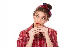 Schöne junge Frau, die Plätzchen isst stockfotos