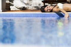 Schöne junge Frau, die am Poolside ein Sonnenbad nimmt Lizenzfreie Stockbilder