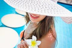 Schöne junge Frau, die am Rand des Pools sitzt Stockfotografie