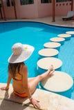 Schöne junge Frau, die am Rand des Pools sitzt Stockfotos